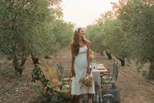 Delighted Bride Standing Near Banquet Table In Summer Garden