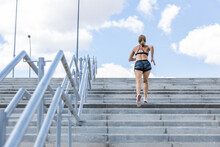 Rear View Of A Young Woman Running While Climbing The Stairs