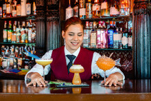 Cheerful Barman Serving Creative Cocktails In Bar