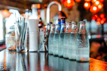 Glass Bottles With Cold Water On Counter In Bar