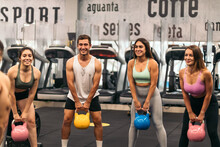 Fitness Class Lifting Kettlebells In A Gym.
