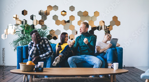 Fotografía Excited man interacting with diverse colleagues on couch in house
