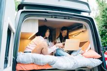 Diverse Girlfriends Using Laptop In Camper Van