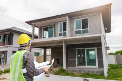 professional engineer in protective helmet and blueprints paper at the house bui Fototapet