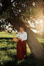 Charming Woman In Vintage Clothes With Basket Of Fruits