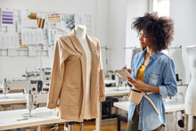Positive African-American Tailor In Denim Shirt Writes In Notebook Looking At Mannequin With Jacket In Workshop