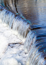 Water Cascades Over A Spillway On A River In Wisconsin On A Sunny Day.