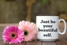 Inspirational Message On A White Mug - Just Be Your Beautiful Self. With Cup Of Coffee Or Tea And Two Pink Daisy Flowers Background. Self Love Care And Confidence Concept.