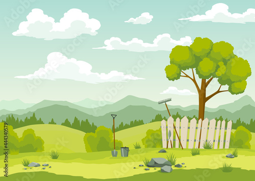 Spring landscape with green grass, hills, blue sky with clouds and farm implements Fototapet