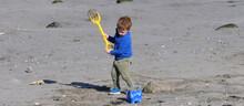 PanoramicRed Headed Boy Building Sandcastles Bucket Spade On A Sandy Beach