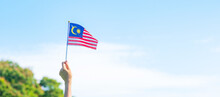 Hand Holding Malaysia Flag On Blue Sky Background. September Malaysia National Day And August Independence Day