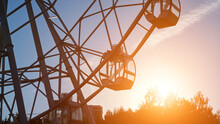 Empty Cabins Of Large Operating Metal Ferris Wheel Amusement Ride Rotate In Local Park Against Sky Over Tree Silhouettes In Evening After Sunset