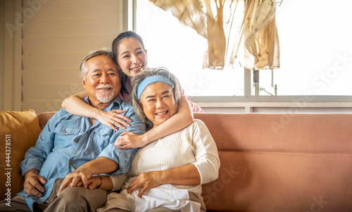 Fotografie, Obraz Daughter hugs father and mother showing love in the living room, happy family