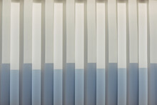 Abstract Geometric Vertical Lines White And Gray Gradient Color. Repeating Pattern, Background Texture, Design Of Striped Lines. Blinds Illuminated By The Sun, Close-up.