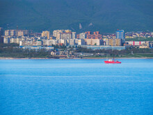 A Red Bright Fire Vessel With A Crane Goes Through The Black Sea In The Tsemesskaya Bay. Cargo Ship On The Background Of The Houses Of The City Of Novorossiysk.