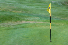 A Yellow Flag On A Pole In A Hole On A Golf Course