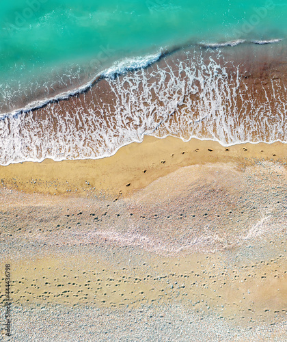 Fotografia Human and dog footprints on a sandy shore along the sea with breaking waves, aer