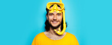 Young Smiling Man In Yellow, Wearing Diving Mask And Snorkel On Blue Background.