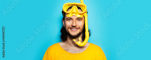 Fotografia Young smiling man in yellow, wearing diving mask and snorkel on blue background