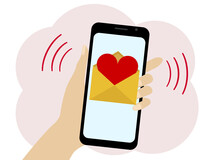 Hand Holds A Mobile Phone With A Picture Of A Letter With A Red Heart