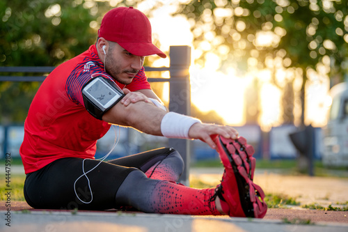 Young fitness man runner stretching legs Fototapet
