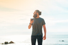 Handsome Bearded Man Holding Mobile Phone In His Hand, Texting Message And Looking Away On Tropical Background.