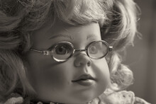 Portrait Of A Vintage Baby Doll, A Toy Girl With Blond Hair And Glasses.