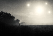 A Moody Science Fiction Concept, Of A Figure Standing In A Field With UFO Lights Glowing In The Sky. On A Foggy Spooky Night. With A Vintage, Grunge Edit