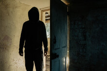 A Horror Concept. Of A Hooded Figure With No Face Standing In The Doorway Of A Decaying Room In An Abandoned Ruined House