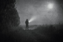 A Moody Atmospheric Concept, Of A Spooky Figure Standing In A Field With A Torch On A Foggy Spooky Night. With A Grunge, Vintage Black And White Edit