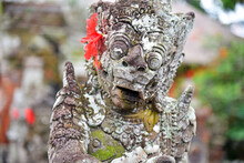 Statue In Taman Ayun Temple With Red Flower On The Ear