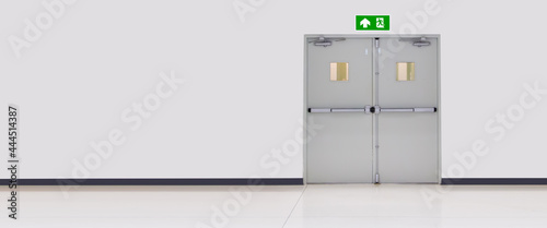 Fotografie, Obraz Green emergency fire exit sign or fire escape with the doorway or door exit in the building concepts for evacuation in the event of a fire