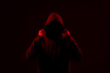 Silhouette Of Anonymous Man On Dark Background, Toned In Red