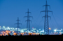 Power Lines In The Evening On The Background Of Blurred City Lights