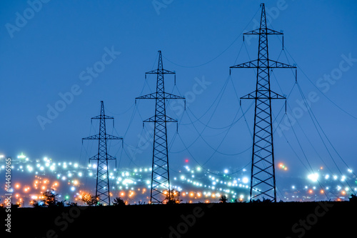 Fotografia power lines in the evening on the background of blurred city lights