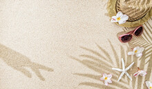 Straw Hat With Frangipani Flowers, Sea Shells And Sunglasses On White  Sand With Palm Tree And Hand Shadow. Summer Concept With Copy Space