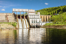 Old Beautiful Concrete Dam Located In A Mountain Gorge. Deep Reservoir. Dark Water. Summer.