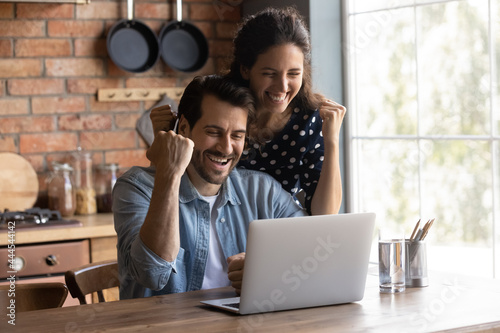 Happy excited young couple making winner yes hand fist gesture at laptop, getting awesome news, celebrating achieve, success, winning prize, getting unexpected income Fototapet