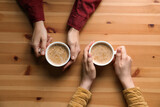 Women with cups of coffee at wooden table, top view