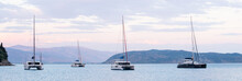Mediterranean Bay With Sailing Boats Catamarans Panoramic Banner. Yachts On A Sea, Corfu Island, Greece, Yachting, Sport, Vacations, Enjoying Life, Summer Fun Travel And Active Lifestyle Concept