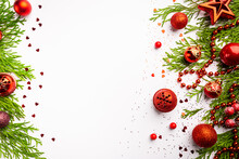 Christmas Red Decorations And Thuja Branches On White Background, Top View With Copy Space. Winter Decoration Background