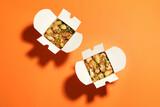Boxes of noodle wok on orange background, flat lay