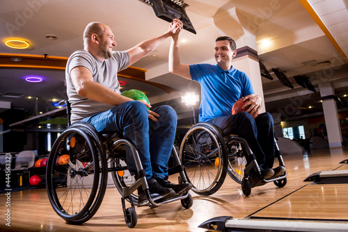 Fotografiet Two young disabled men in wheelchairs playing bowling in the club