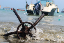A Fishing Boat Anchored By The Beach In St. Martin's Island, Bangladesh. Fishing Boat Rusty Traditional Anchor On A Beach By The Sea. Rusty Anchor Wet Beach Sand And Wave.