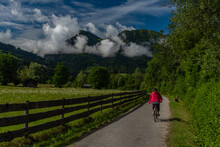 Path With Red Dressed Woman On Bicycle Near Wooden Fence And Color Meadow