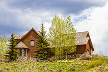 Luxury Log Cabin With Wooden Roof And Rock Bay Window On Hilltop Surrounded By Pines And Quaking Aspens