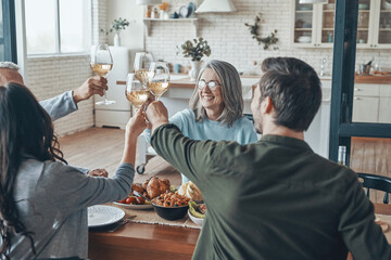 Happy multi-generation family toasting each other and smiling while having dinner together