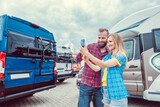 Woman and man taking selfie in front of RV or camper van in anticipation