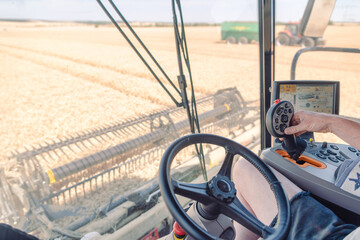 View from the drivers cabin on combine harvester to the grain field