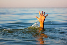 A Man Is Drowning In Water. A Hand Peeks Out From Under A Water. A Drowning Person Needs Help, Rescue. A Risk, Danger For Living In The Sea, River, Ocean, Pond. Death, SOS Concept. Drowning Victim